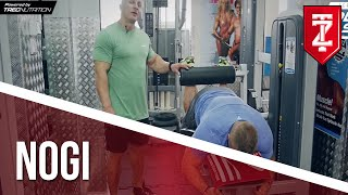 ĆWICZENIA NA NOGI: Uginanie nóg na maszynie leżąc - Tomasz Lech: SOLID MASS (Zapytaj Trenera)