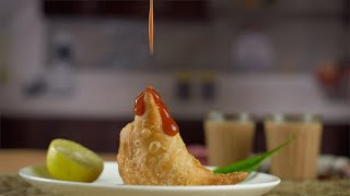 Red tomato sauce poured on a delicious samosa stuffed with potato filling - Indian cuisine
