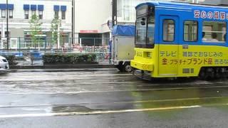 大雨で水たまりができた軌道を水しぶきを上げてを強行突破する阪堺電軌1
