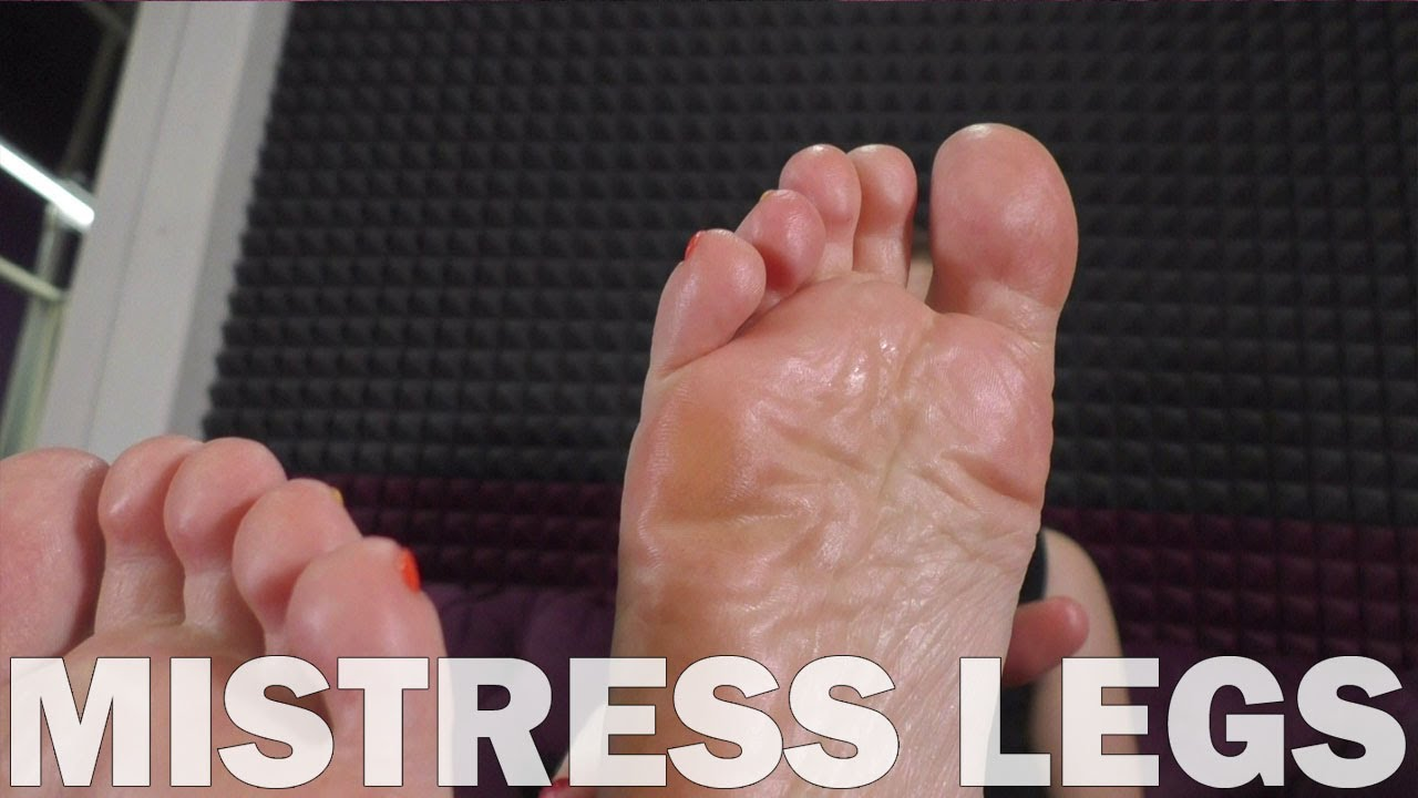 Mistress smears her feet with cream