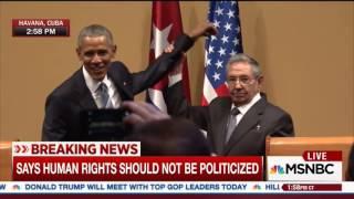 Raul Castro raises President Obama's limp arm
