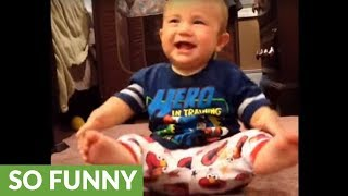 Laughing baby falls over from excitement