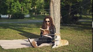 Attractive girl student is reading book sitting on plaid under tree in city park with her puppy
