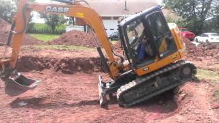 Heavy equipment trick track hoe dropping in