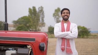 Young attractive farmer happily standing beside his brand new tractor