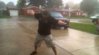 Chris Hight in the pouring rain air guitaring.