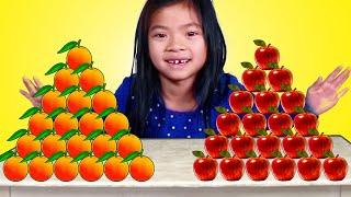 Emma giả vờ chơi với nhiều cam và táo