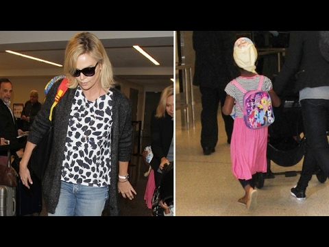 Charlize Theron Catches Flight As Son Jackson Dons Pink Skirt