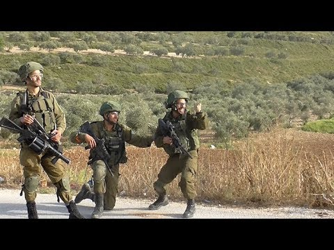 Israeli soldiers cheer after shooting a Palestinian protester in the village of Madama