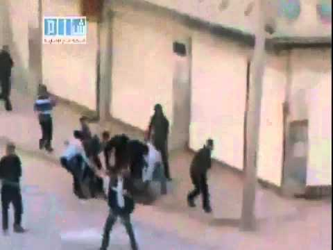 Syria - Homs - City - 20110427 - Group runs to a wounded protester to beat him.