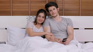 Young happy couple lying on bed and watching television together