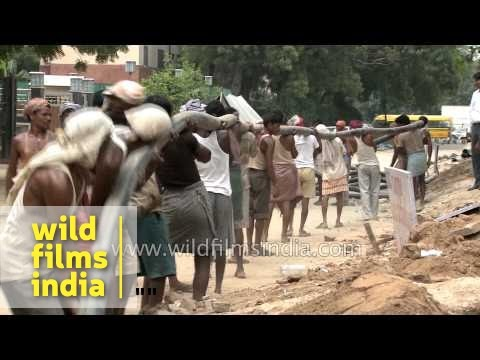 Indian workers relocate a heavy cable wire - Delhi