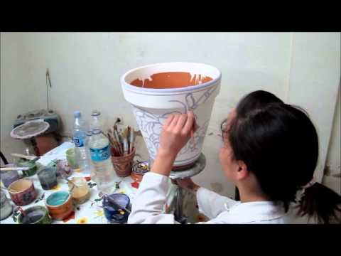 Hand painting a garden pot in Andalucia, Spain