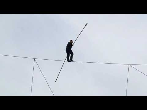 Daredevil walks on high wire between two building at the National Harbor
