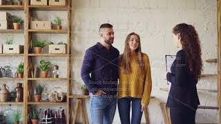 Female realtor in suit is showing loft style flat to young man and woman looking for new apartment