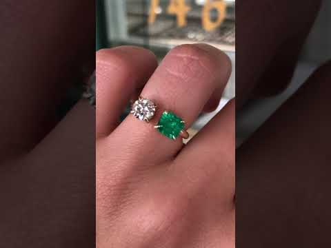 Two stone emerald cut emerald and round diamond solitaire ring 18K