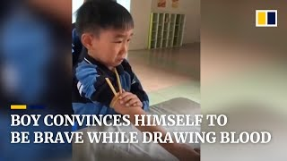 Cute boy convinces himself to be brave while while drawing blood in China