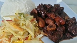 One Of The Best Jamaican Oxtail Recipes Served With Plain Rice And Stir Fry Cabbage.
