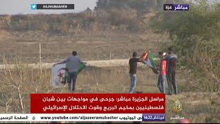 شاب في غزة يلوح بعلم الجزائر أمام قوات الاحتلال الإسرائيلية