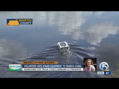 Volunteer uses sonar equipment to search canal