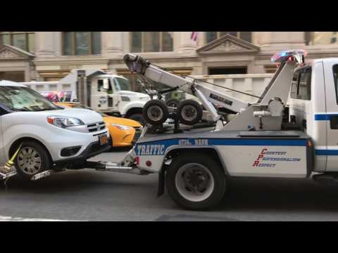 NYPD TOW TRUCK TOWING A CAR ON 5TH AVENUE IN THE MIDTOWN AREA OF MANHATTAN IN NEW YORK CITY.