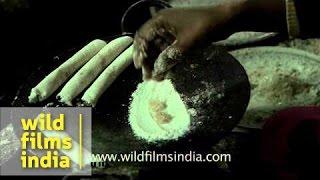 Woman prepares Pitha (Assamese rice cake) on eve of Bhogali Bihu