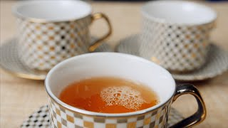 Slow motion shot of black tea being poured into a cup with the help of teapot