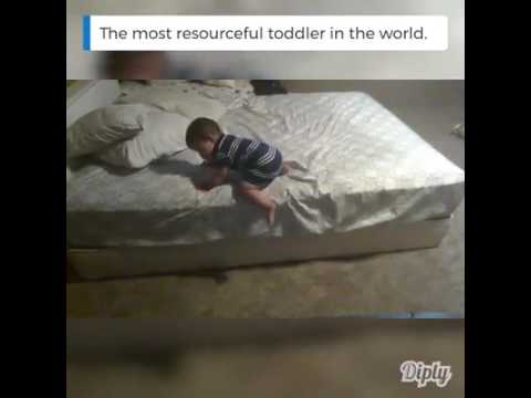 A 1 Year Old Child Trying to Get Down of Bed