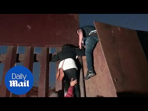 Migrants seen jumping US border fence under cover of darkness