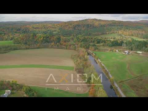 Fly over Ammonoosuc River, by farms, colorful trees, autumn, Lisbon, New Hampshire | AX150_268