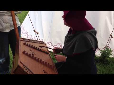Someone playing a Medieval instrument