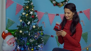 Pretty young girl using her mobile phone while doing Christmas preparations at home