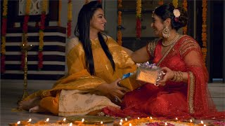 Diwali Celebration - Mother and daughter in colourful Indian dresses exchanging gifts