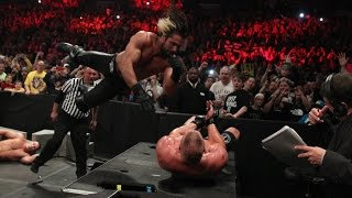 Seth Rollins hits a flying elbow drop onto the announce table: Slow Mo Replay from Royal Rumble 2015