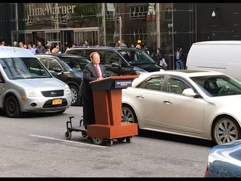 Melissa McCarthy as Sean Spicer podiums on a NYC street, May 12, 2017