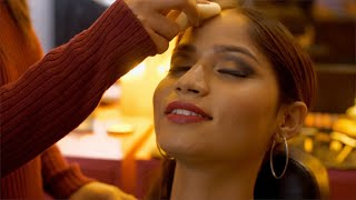 A professional makeup artist is applying foundation on the face of a young Indian model