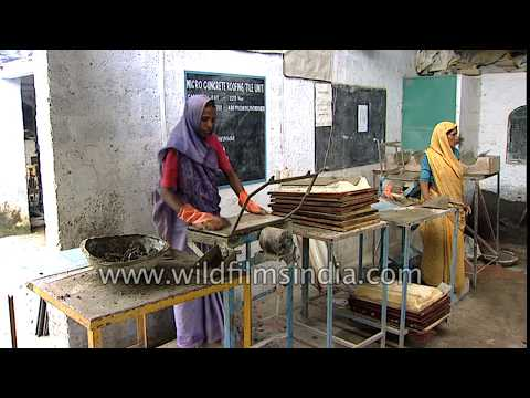 Indian women labourers make micro concrete roofing tiles in India
