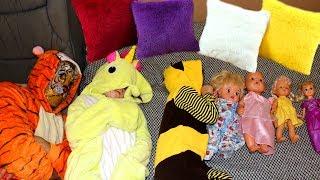 Детки играют с куклами и укладывают их спать