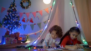 Young happy children coloring together while lying in their tent during Christmas season