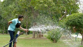 A young man and his kid sprinkling water over big trees in a garden - leisure time