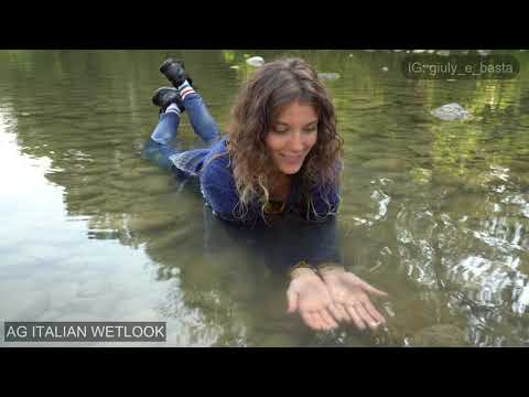 Giulia into the river with black Nike, white socks, jeans, blue sweater