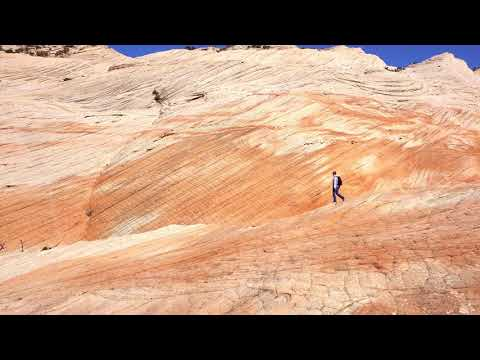 Panning view of woman hiking through color desert landscape layers