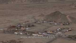 Barren mountains in Ladakh with a patch of houses on hill slope