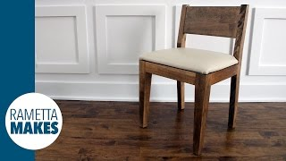 Make a modern designed wood dining chair out of solid birch, with an upholstered leather seat.