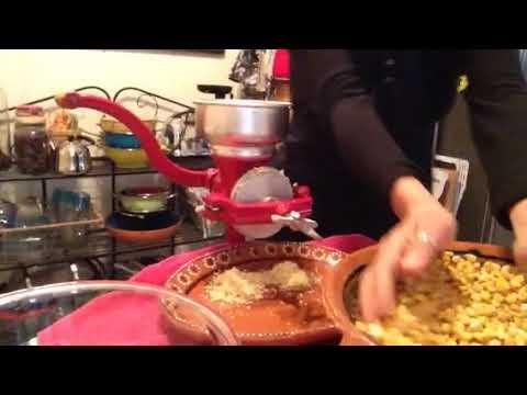 Manually grinding non-GMO corn.