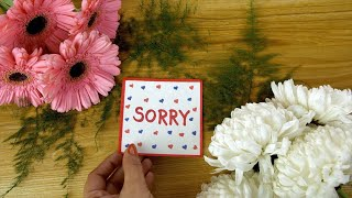 Woman hands placing a colorful handmade sorry card on a decorated wooden surface