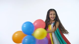Beautiful Indian girl playing with a bunch of colorful balloons in a pretty casual clothing