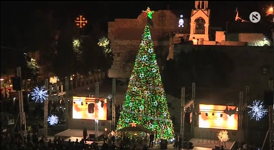 Palestinians light up a Christmas tree in the West Bank town of ...