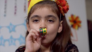 Cute Indian girl blowing blow out whistle at a birthday party
