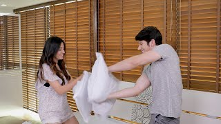 Young couple pillow fighting in their bedroom